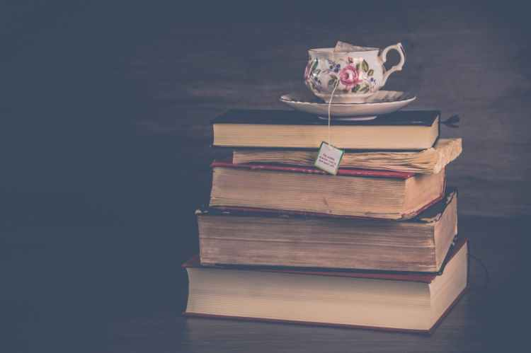pile of hardbound books with white and pink floral ceramic teacup and saucer
